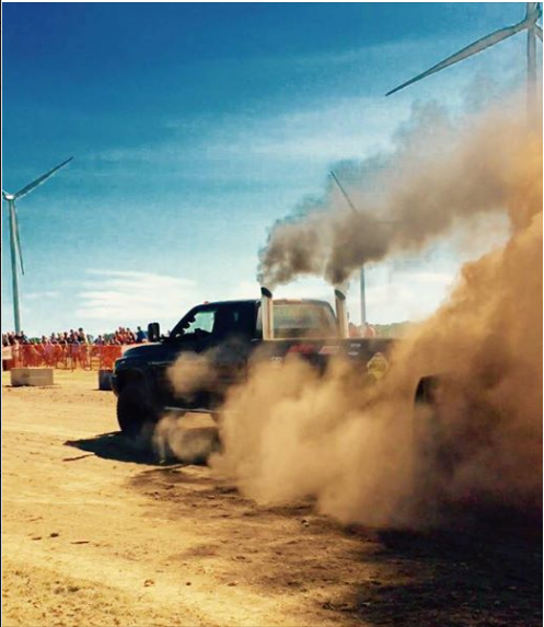 Pulling truck with cloud of dirt